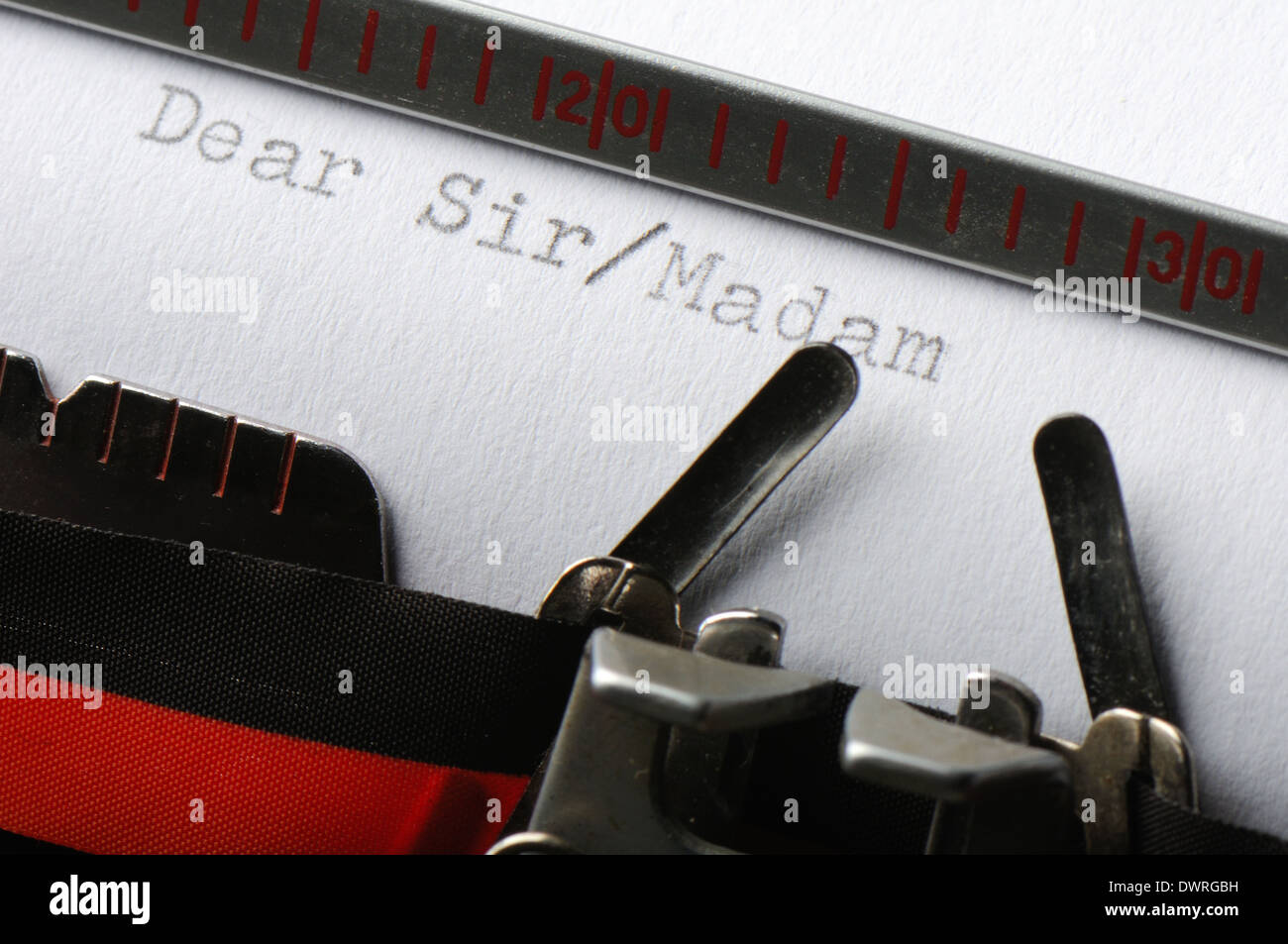 Close-up of old typewriter ribbon and type font on a sheet of paper. - Stock Image