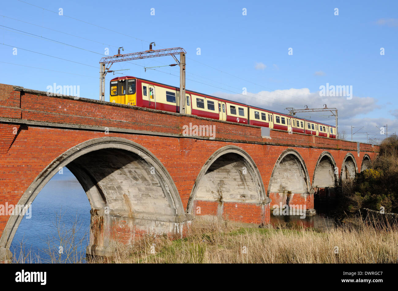 Network rail viaduct with electrified line and First train - Stock Image