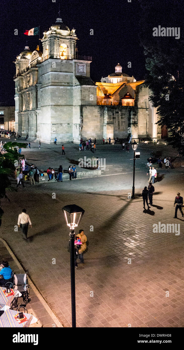 scene at night looking down on Zocalo with view of illuminated Cathedral & plaza with children playing people socializing Oaxaca - Stock Image