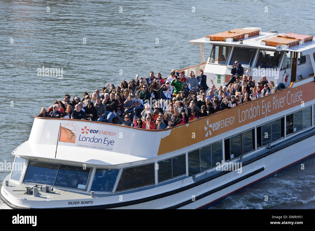 Tourists cruising on the Thames river in a pleasure boat, London, England, United Kingdom. - Stock Image