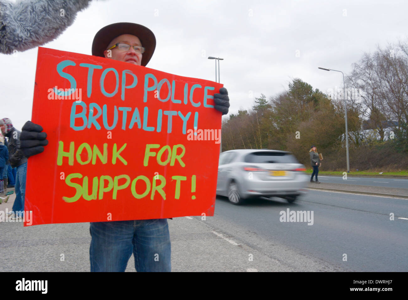 Barton Moss anti-fracking protesters holding sign about Greater Manchester Police  Tactical Aid Unit brutality against them - Stock Image