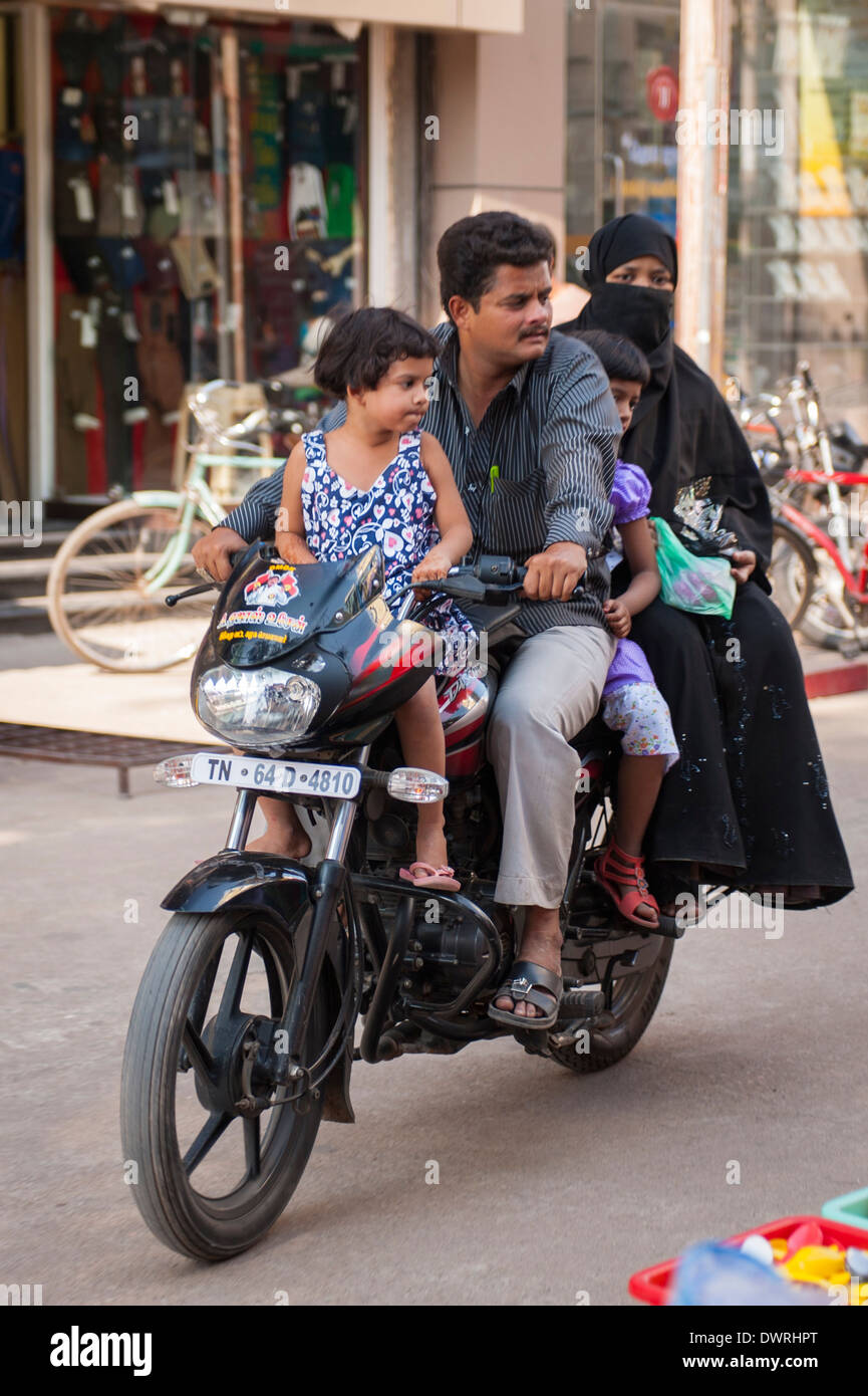 South Southern India Tamil Nadu Madurai street scene Muslim family 4 four on motorbike mother father 2 two children Stock Photo