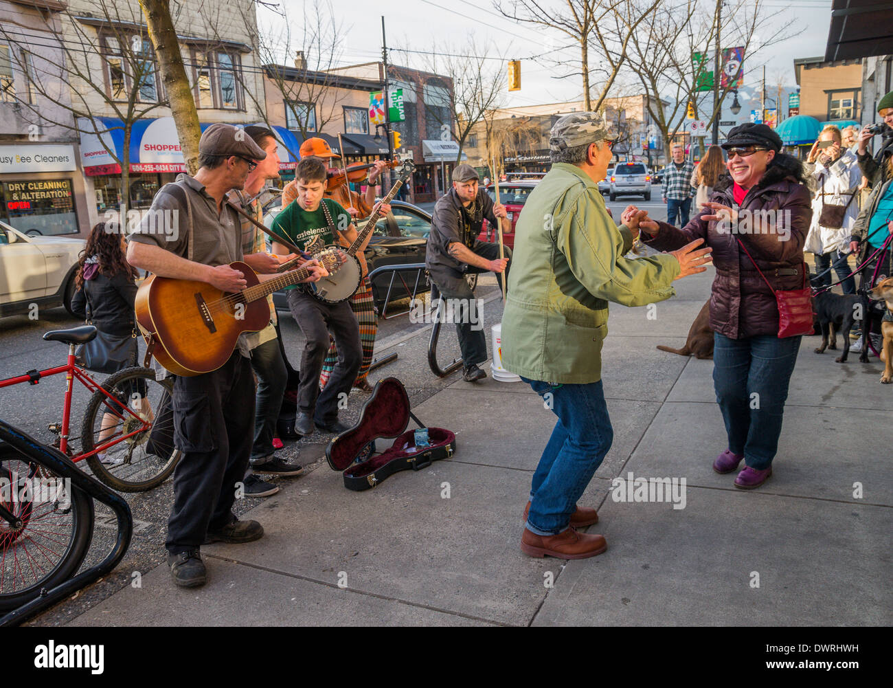 Couple dancing on the street to music of buskers, Commercial Drive, Vancouver, British Columbia, Canada. - Stock Image