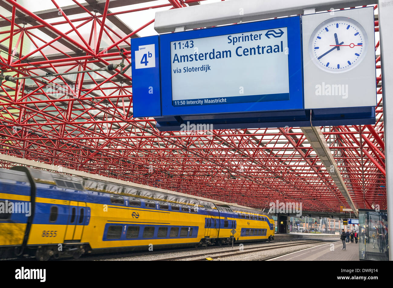 Railway station at Zandaam, near Amsterdam Centraal, Netherlands with a train passing through - Stock Image