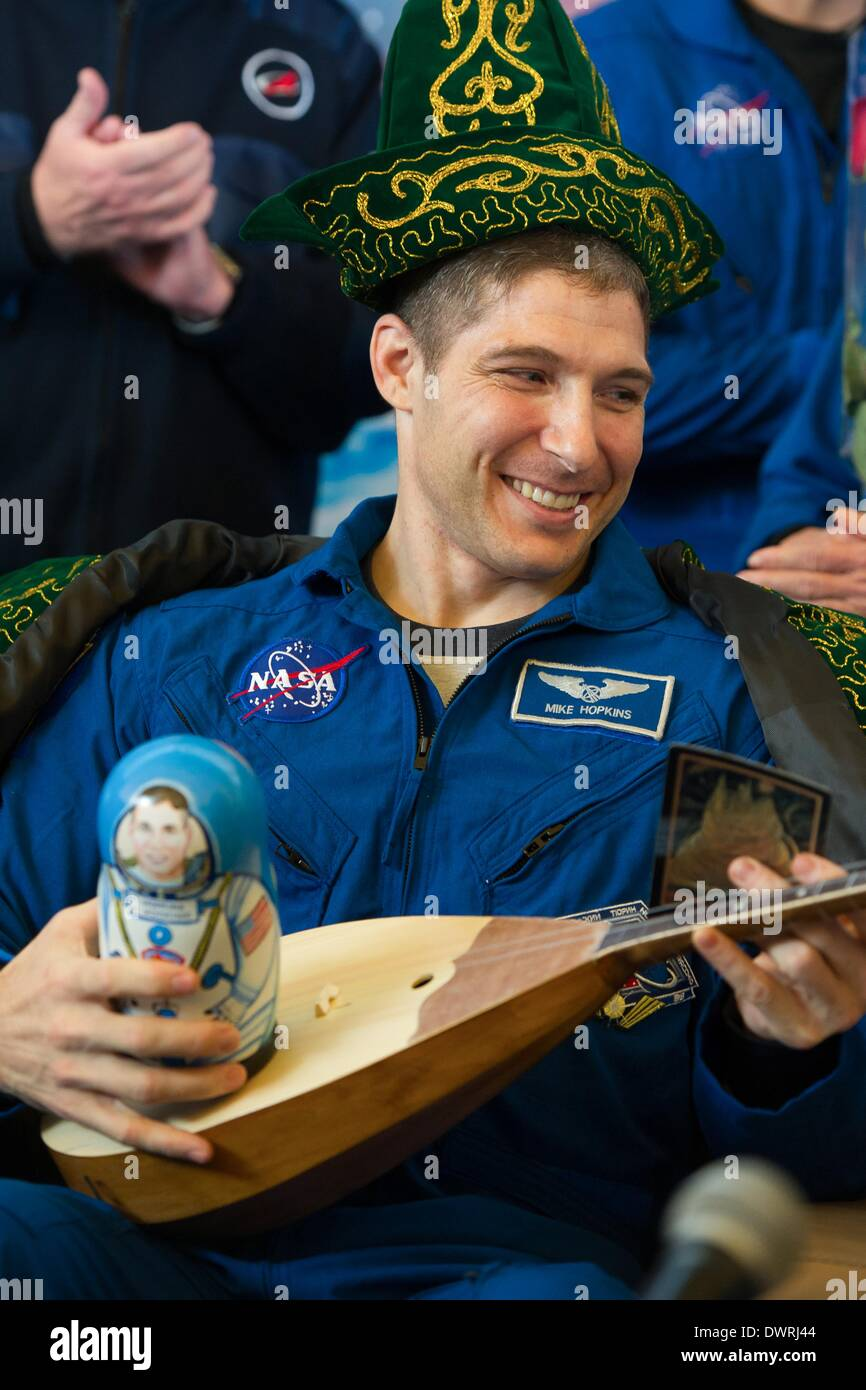 Karaganda airport, Kazakhstan. 11th March, 2014. International Space State Expedition 38 astronaut Mike Hopkins of NASA smiles with his gifts of traditional Kazakh clothing and a matryoshka doll during a welcoming ceremony after landing in a Soyuz TMA-10M spacecraft March 11, 2014 held at the Karaganda airport, Kazakhstan. Hopkins, Kotov and Ryazanskiy returned to Earth after five and a half months onboard the International Space Station. Credit:  Planetpix/Alamy Live News - Stock Image
