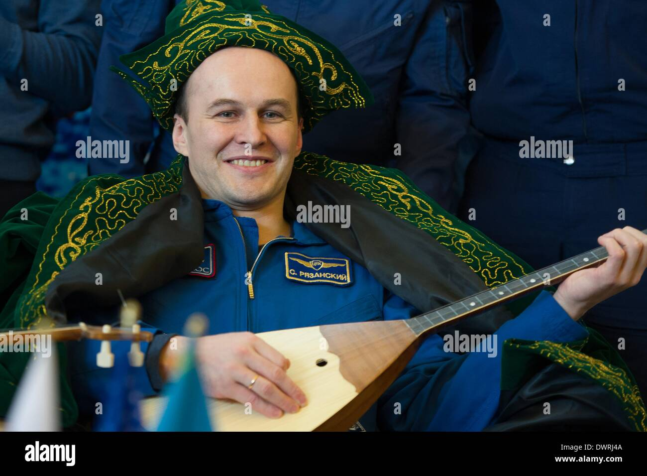 Karaganda airport, Kazakhstan. 11th March, 2014. International Space State Expedition 38 Sergey Ryazanskiy of the Russian Federal Space Agency smiles with his gifts of traditional Kazakh clothing and a matryoshka doll during a welcoming ceremony after landing in a Soyuz TMA-10M spacecraft March 11, 2014 held at the Karaganda airport, Kazakhstan. Hopkins, Kotov and Ryazanskiy returned to Earth after five and a half months onboard the International Space Station. Credit:  Planetpix/Alamy Live News - Stock Image