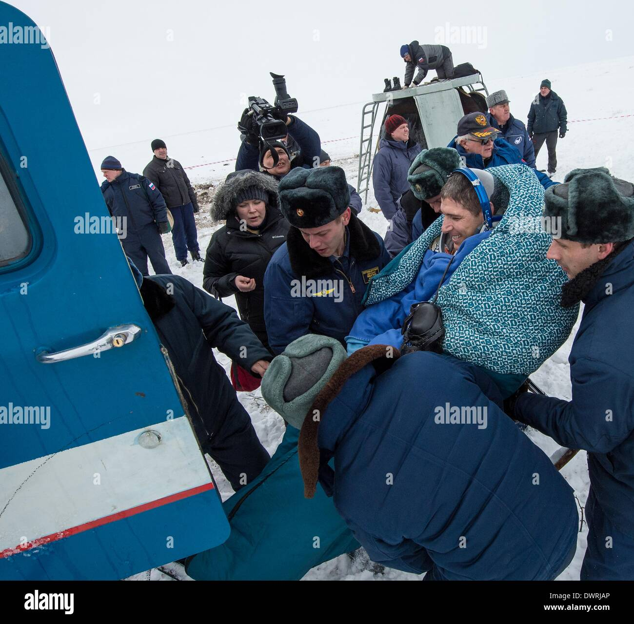 Karaganda airport, Kazakhstan. 11th March, 2014. International Space State Expedition 38 astronaut Mike Hopkins of NASA is helped into a Russian Search and Rescue all terrain vehicle from the Soyuz Capsule after landing in a Soyuz TMA-10M spacecraft March 11, 2014 near the town of Zhezkazgan, Kazakhstan. Hopkins, Kotov and Ryazanskiy returned to Earth after five and a half months onboard the International Space Station. Credit:  Planetpix/Alamy Live News - Stock Image