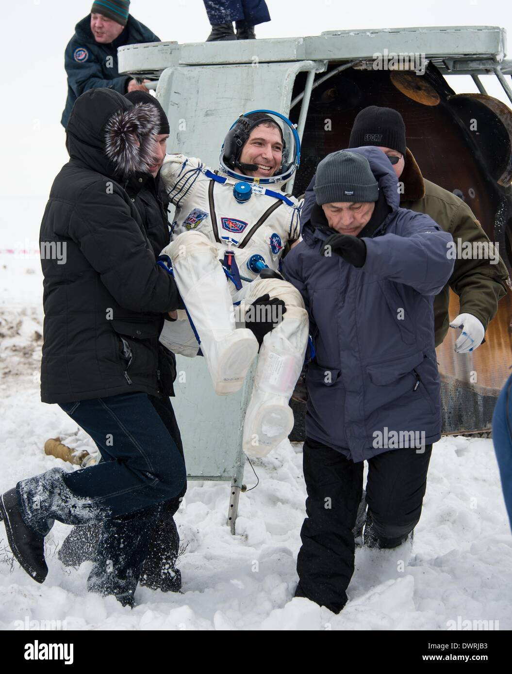 Karaganda airport, Kazakhstan. 11th March, 2014. International Space State Expedition 38 astronaut Mike Hopkins of NASA is lifted out of the Soyuz Capsule after landing in a Soyuz TMA-10M spacecraft March 11, 2014 near the town of Zhezkazgan, Kazakhstan. Hopkins, Kotov and Ryazanskiy returned to Earth after five and a half months onboard the International Space Station. Credit:  Planetpix/Alamy Live News - Stock Image