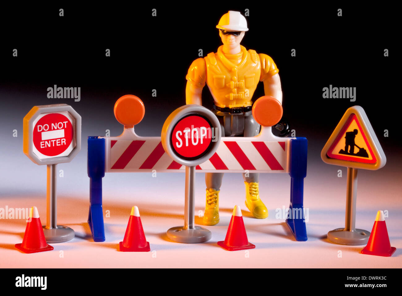 road repairs toy worker with road signs cones and barrier