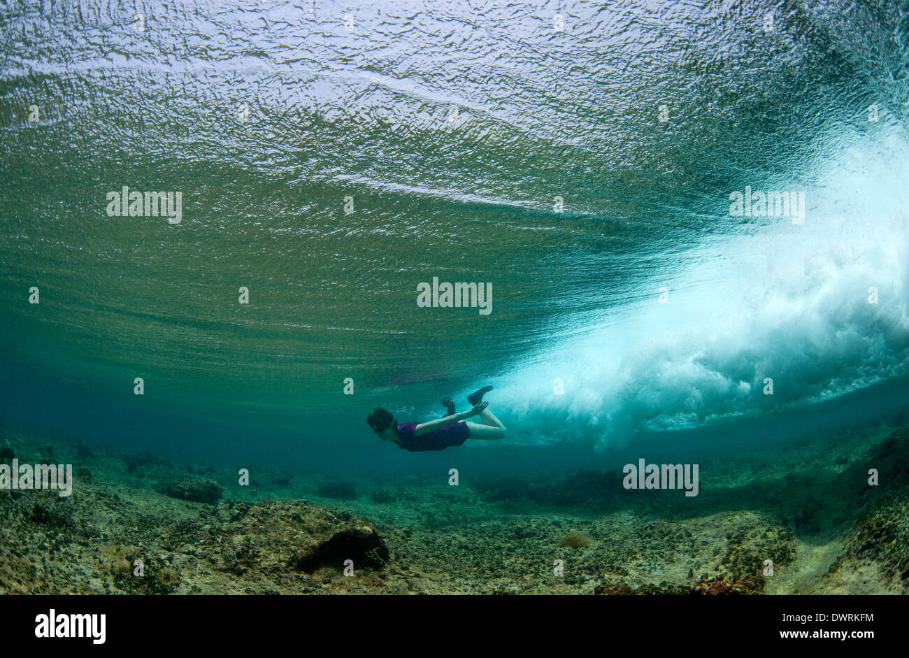 Female swimming through a wave - Stock Image