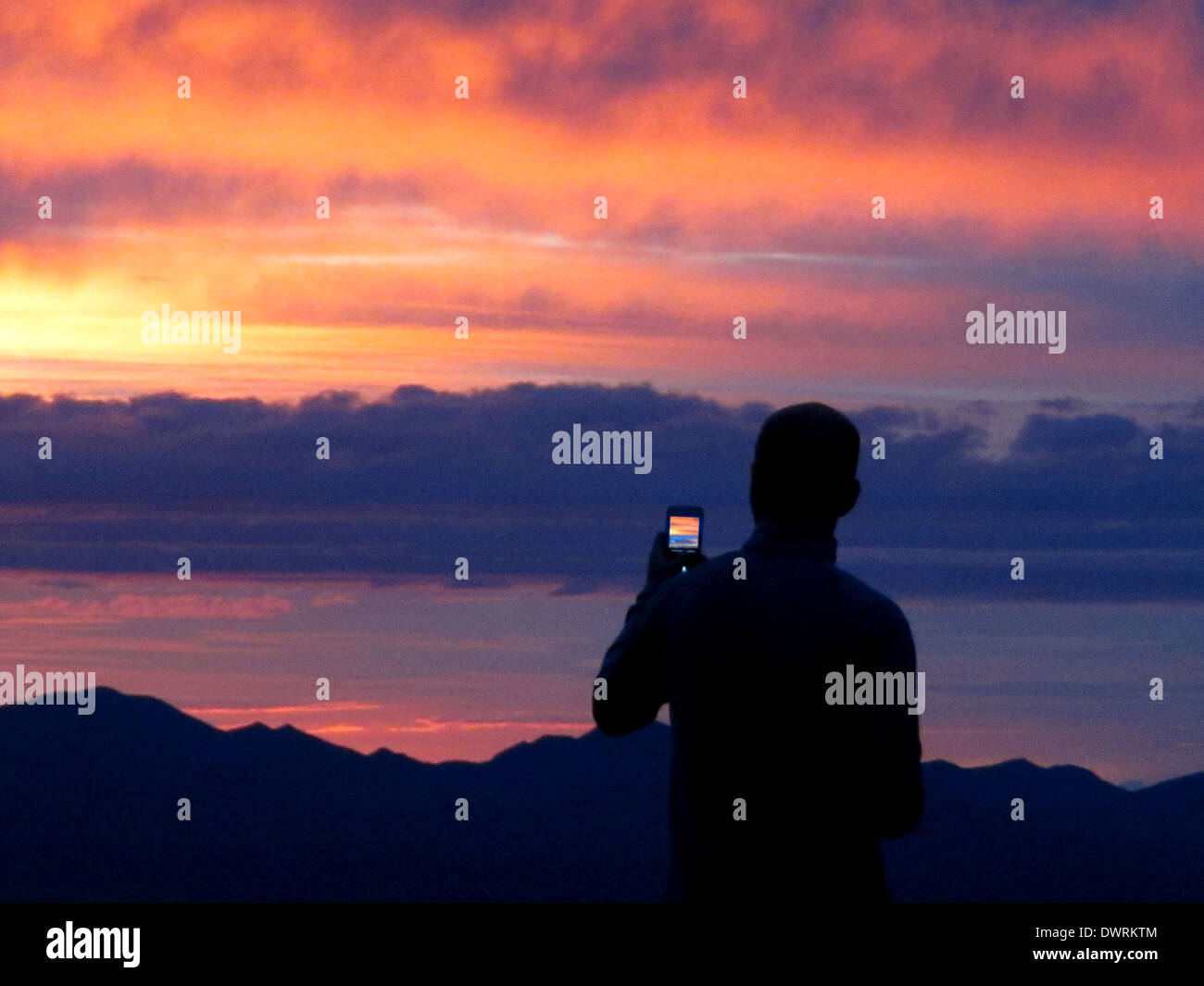 A man takes a photograph of a sunset on his cell phone. - Stock Image