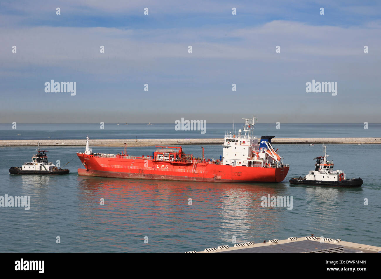 LPG tanker SYN ZAURA being manoeuvered in Livorno harbor by local tug boats - Stock Image