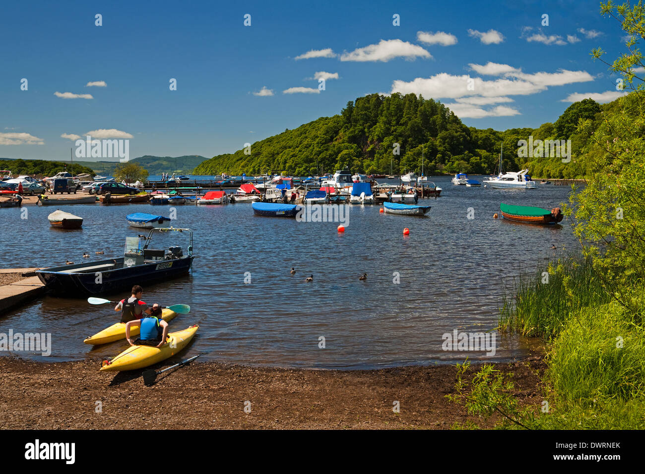 Kayaking at Balmaha Boatyard on Loch Lomond. Inchcailloch is in the background. - Stock Image