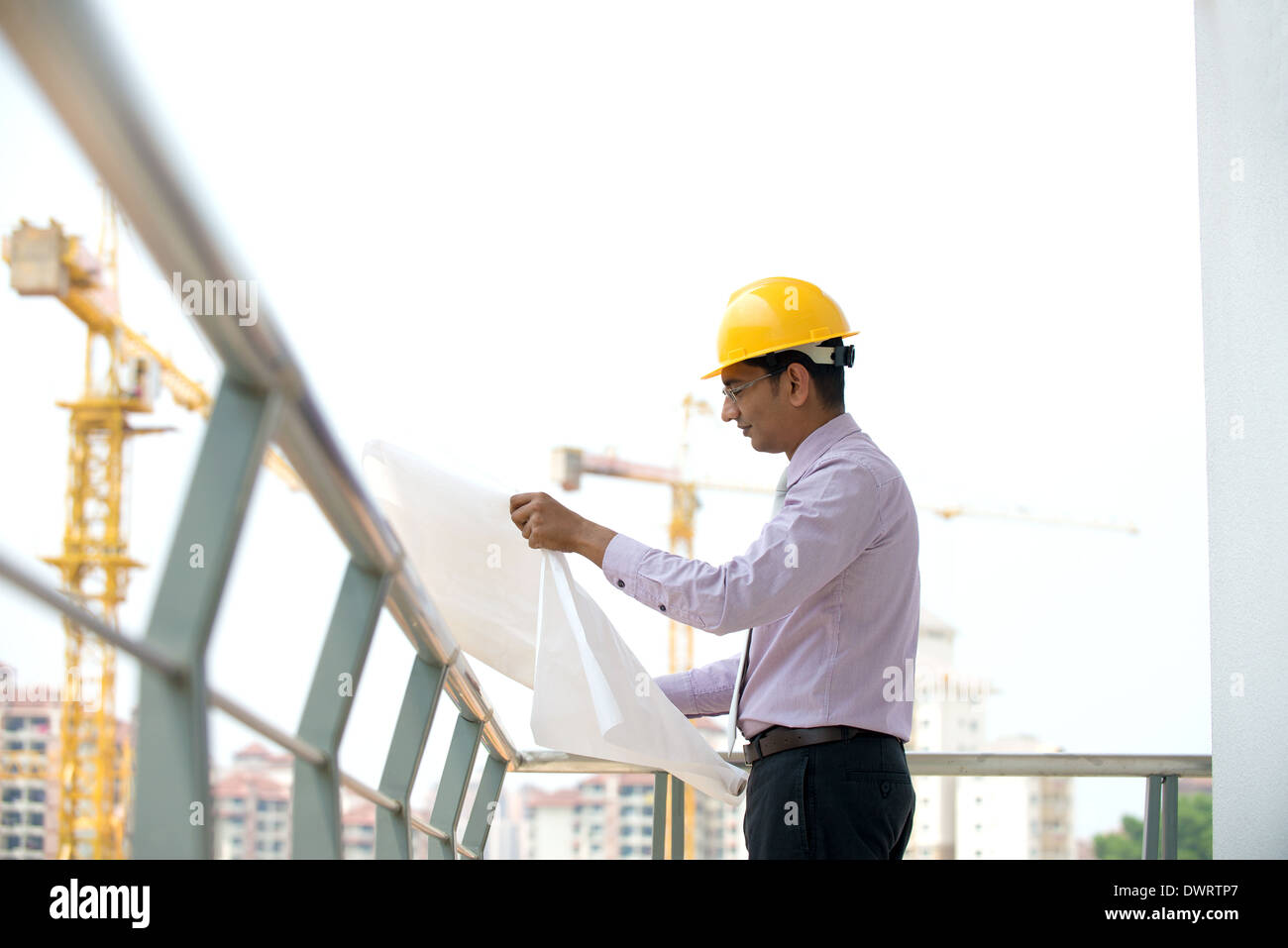 e16a237c720 indian male architect reading plans with construction background ...