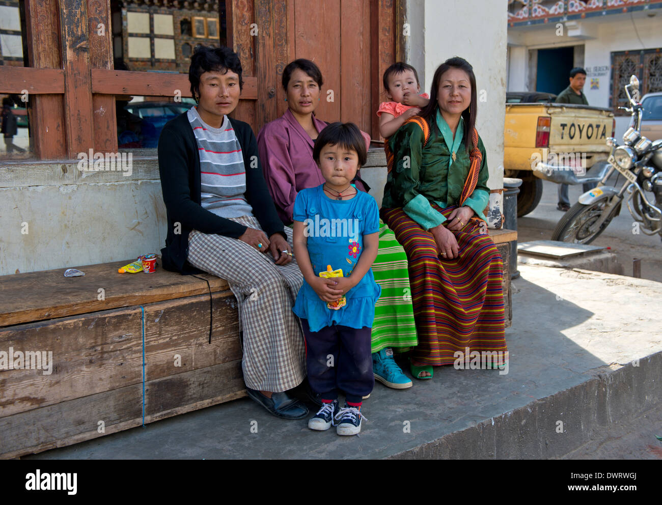 Mothers in national costumes with children sitting on a bench in the main street of Paro, Bhutan - Stock Image