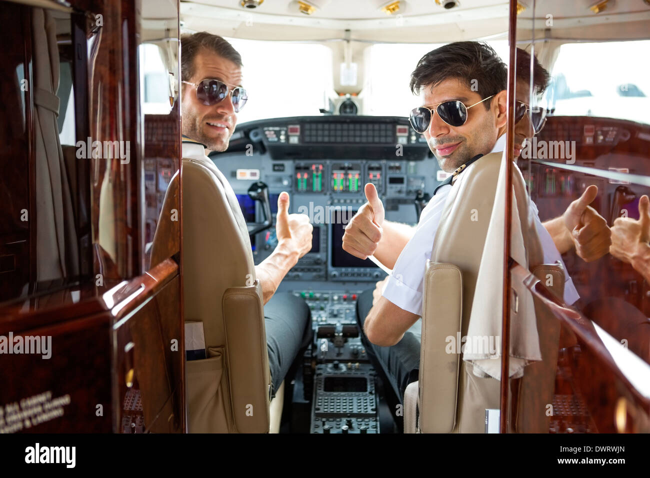 Pilots Gesturing Thumbs Up In Cockpit - Stock Image