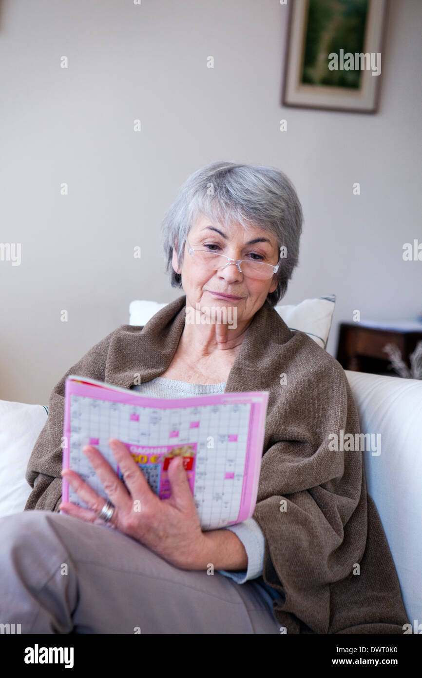 Elderly person doing cr-word puzzle - Stock Image