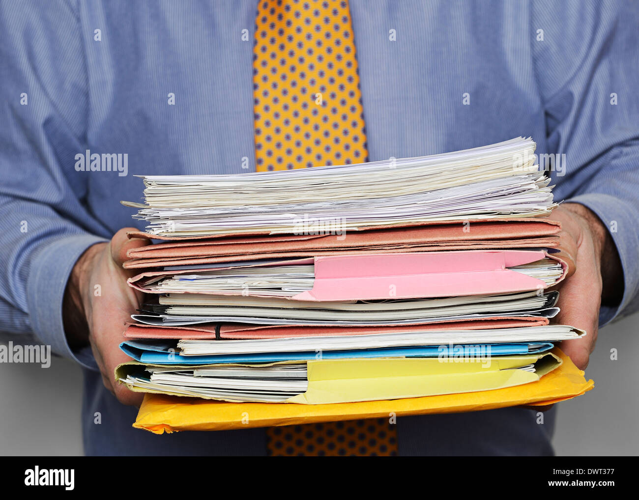 Overworked Businessman Carrying a Stack of Paperwork. Close Up. - Stock Image