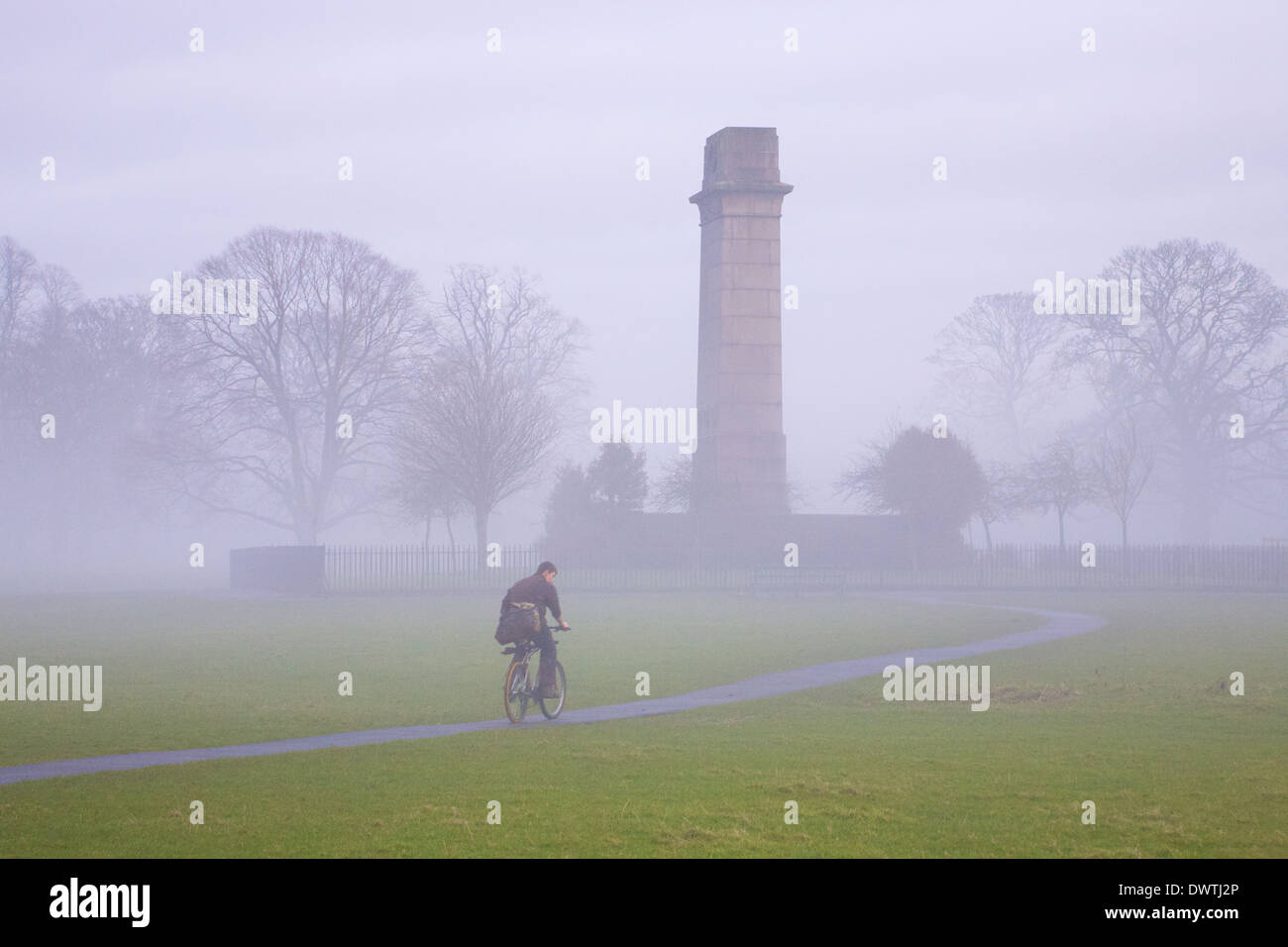 Man cycling on a path towards Cenotaph World War One memorial in the fog. Rickerby Park Carlisle, Cumbria, England. - Stock Image
