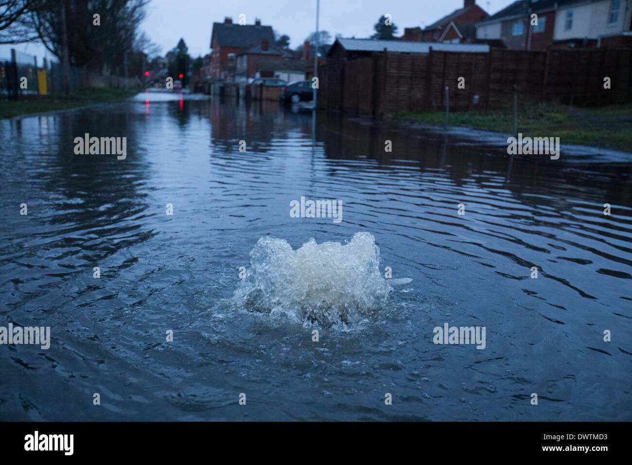 Flood water bubbling up through a drain in Worcester, UK, after the River Severn burst its banks. - Stock Image