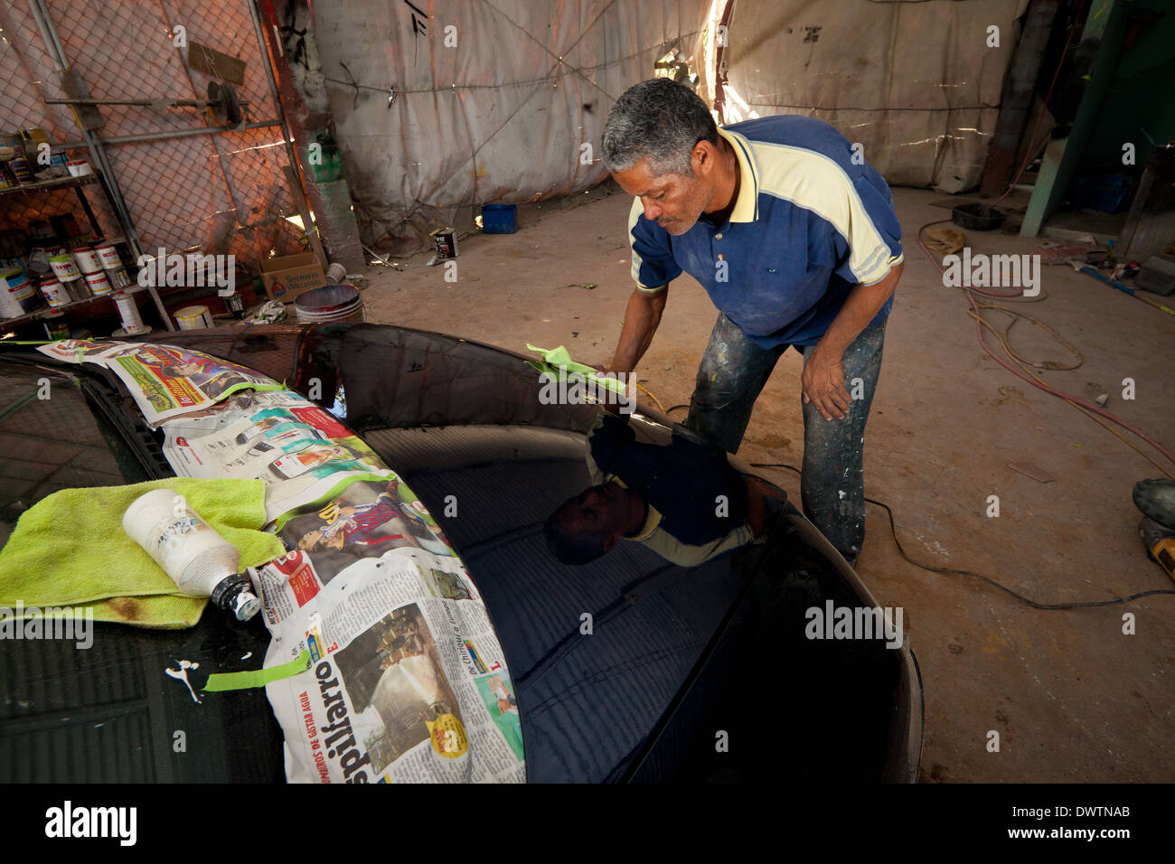 The owner of a car workshop, Santos, polishes a car in Penonome, Cocle province, Republic of Panama. - Stock Image