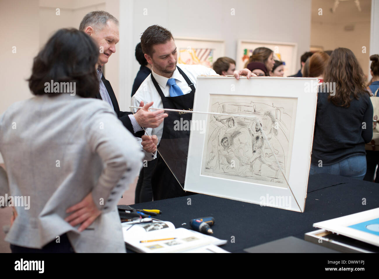 Sotheby's, New Bond Street, London, UK 13th March, 2014. Sotheby's auction of Prints & Multiples, Old Master, Modern and Contemporary, London, UK A curator takes PABLO PICASSO 1881 - 1973 LE COMBAT DANS L'ARÈNE (B. 301; BA. 629) Drypoint, 1937, signed in pencil, numbered 32/50, on Montval laid paper with the Vollard and Picasso watermarks out of it's frame for a collector to view. Estimated at £7,000 - 9,000. Credit:  Jeff Gilbert/Alamy Live News - Stock Image