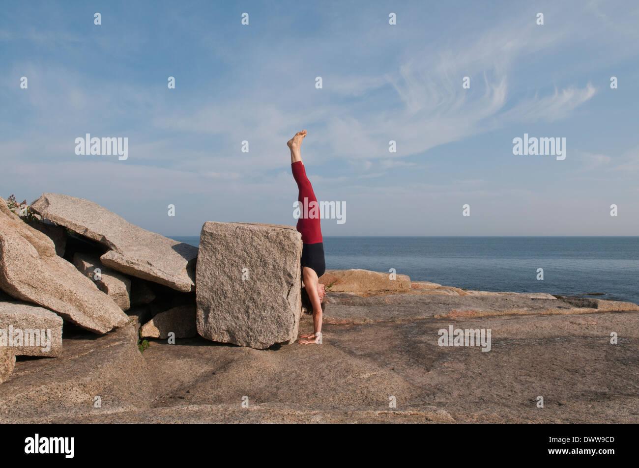 Iyengar Yoga Instructor Demonstrates Adho Mukha Vriksasana (Inverted). Stock Photo