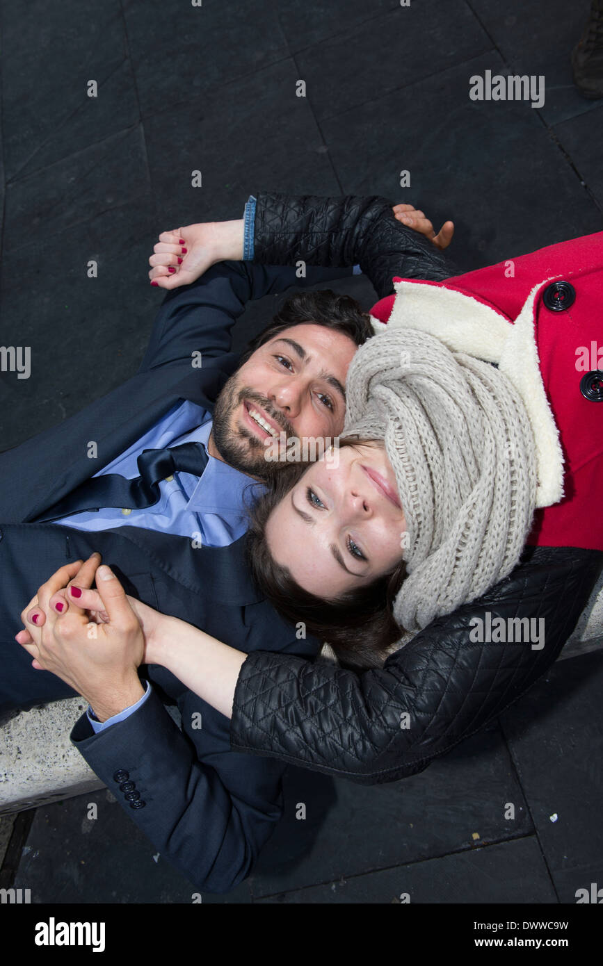 Man and woman lied down on a bench Stock Photo