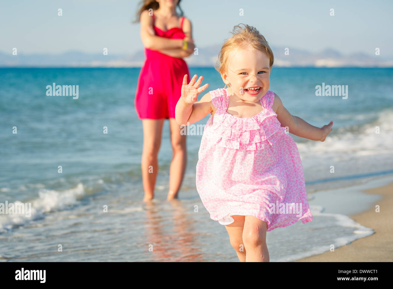 Little girl running on the beach - Stock Image