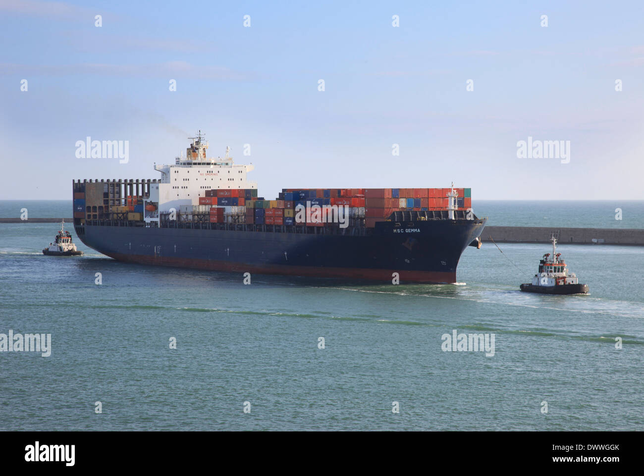 Container ship MSC Gemma arriving Civitavecchia harbor Italy assisted by two tugs - Stock Image
