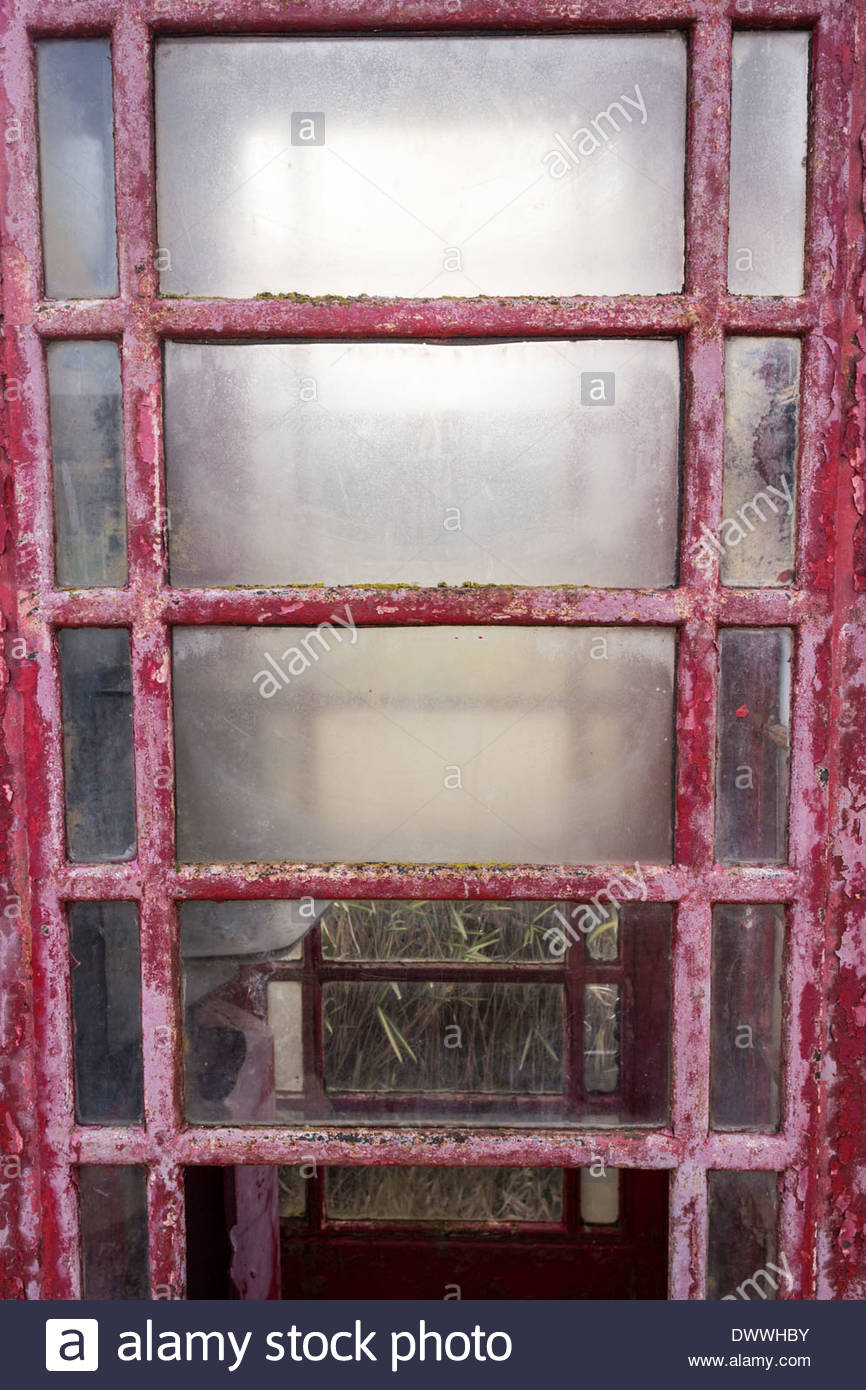 Old and weathered door panel of telephone kiosk - Stock Image