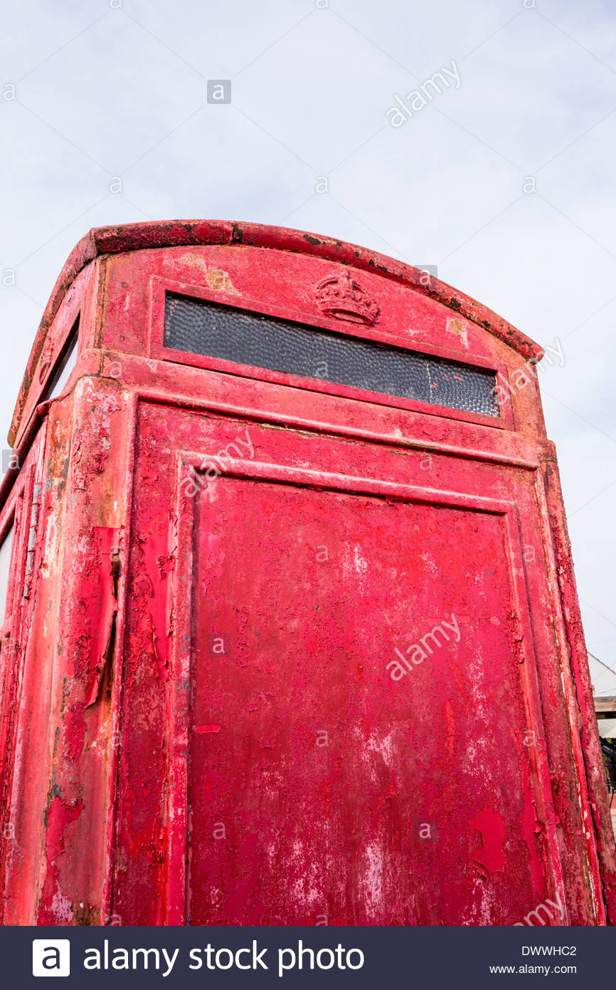 Old and weathered red telephone box with peeling paint - Stock Image