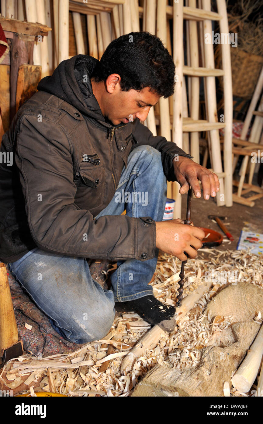 Woodworker in workshop drilling hole with hand auger bit in wood for chair part, Marrakech, Morocco, North Africa Stock Photo