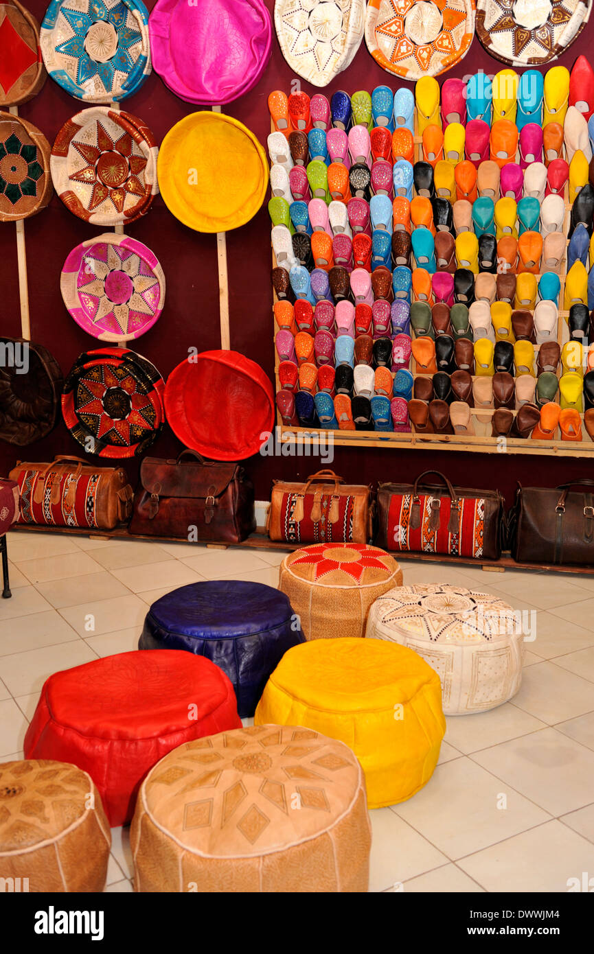 Leather goods, pouffes, shoes, bags, for sale in stall of Marrakech souk - Stock Image