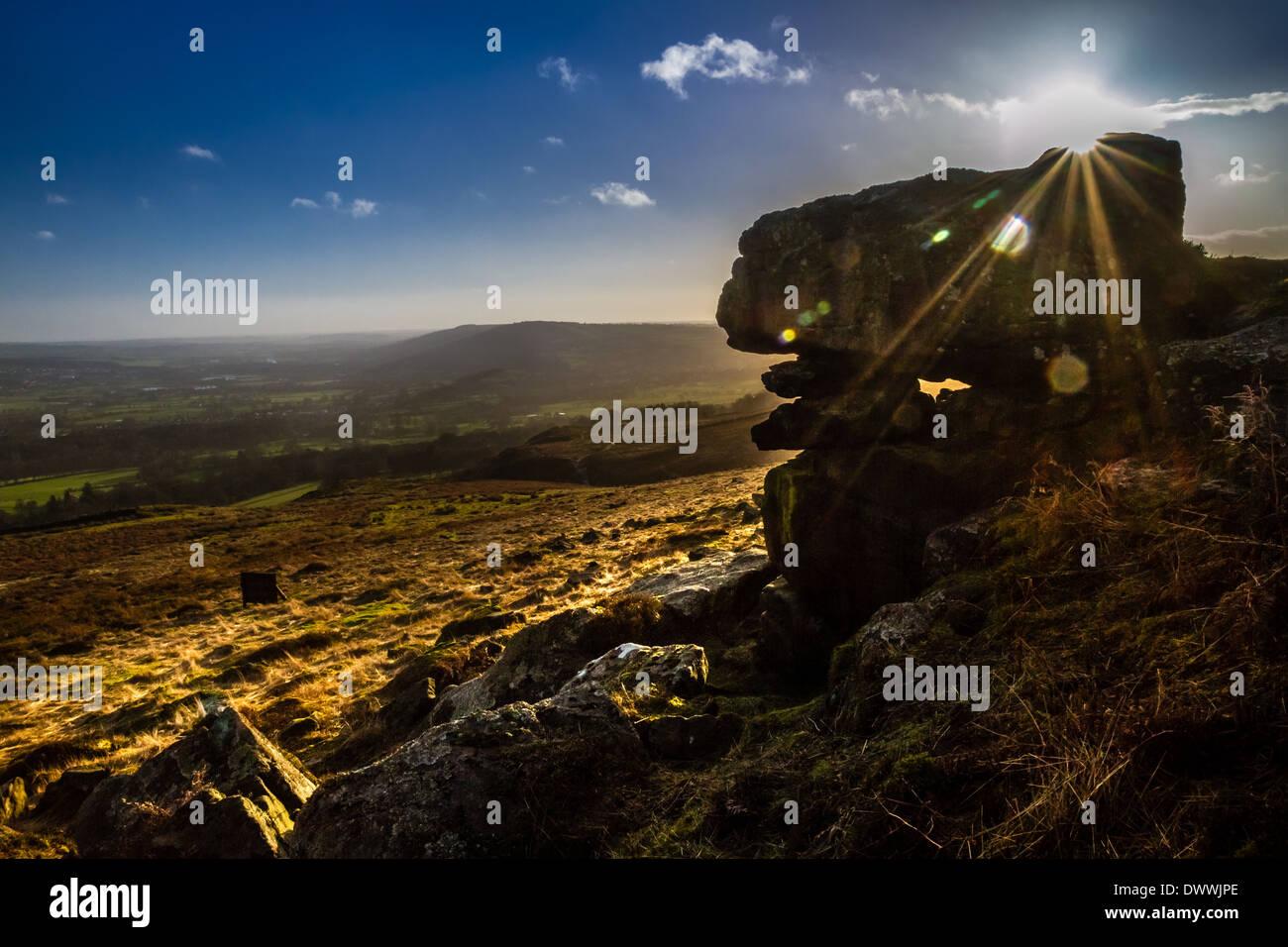 Rural Yorkshire: Sunburst over rocks on the beautiful Ilkley Moor, UK - Stock Image