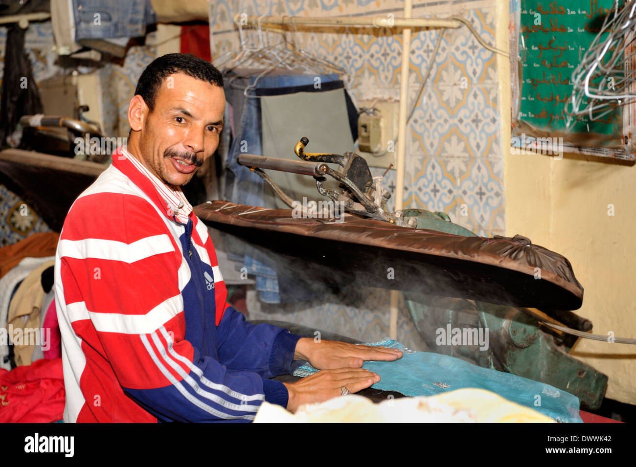 Moroccan man ironing a dress with press in Marrakech souk, Morocco - Stock Image