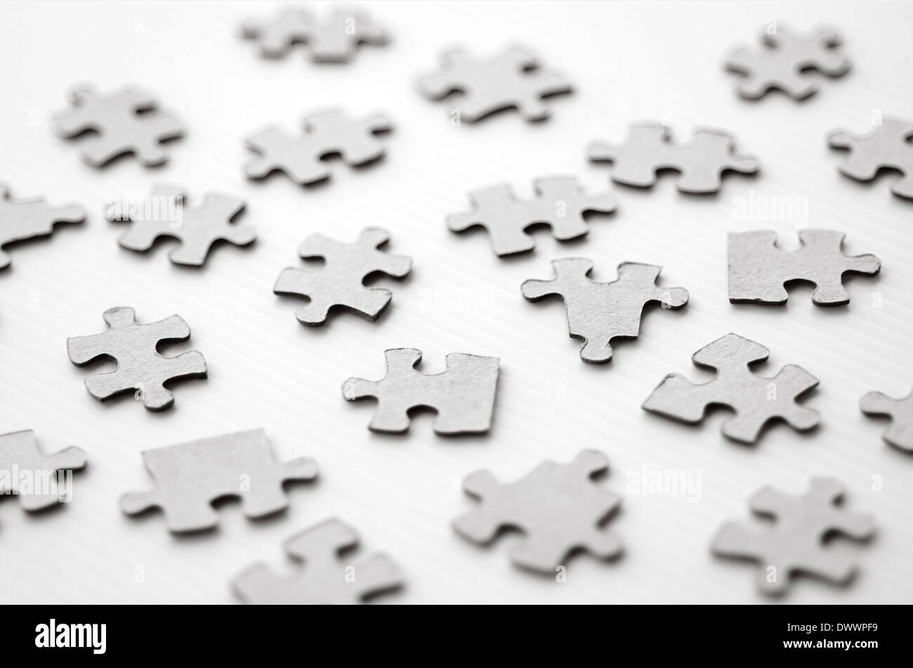 Scattered puzzle pieces toy isolated on white background. Concept photo of disharmony, change, no-order and chaos. (BW) - Stock Image