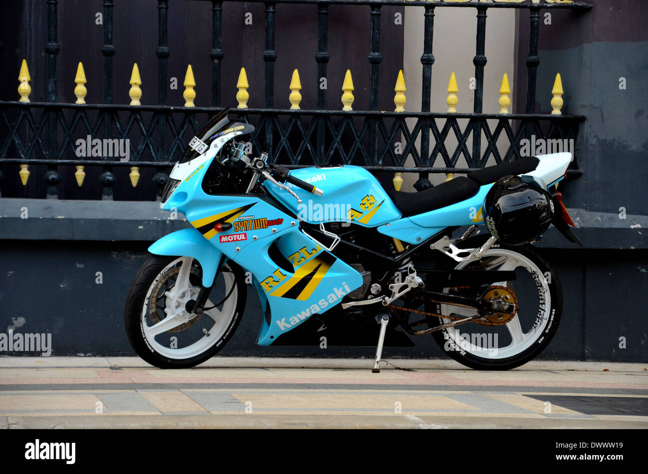 Blue yellow sporty Kawasaki motorcycle parked on pavement with Rizla and Petronas ads Stock Photo