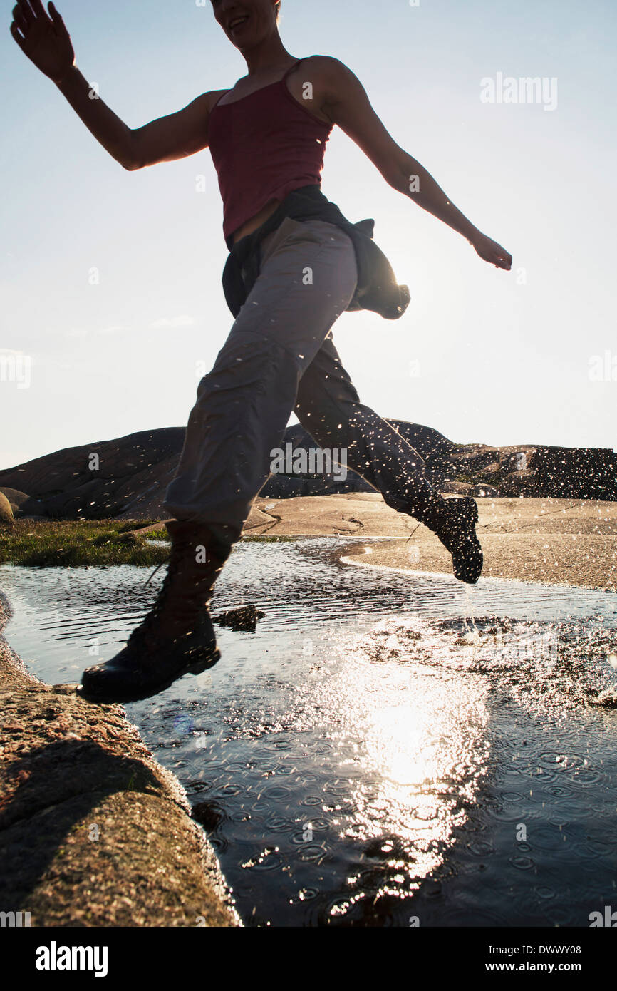 Mid adult woman running over lake during summer - Stock Image