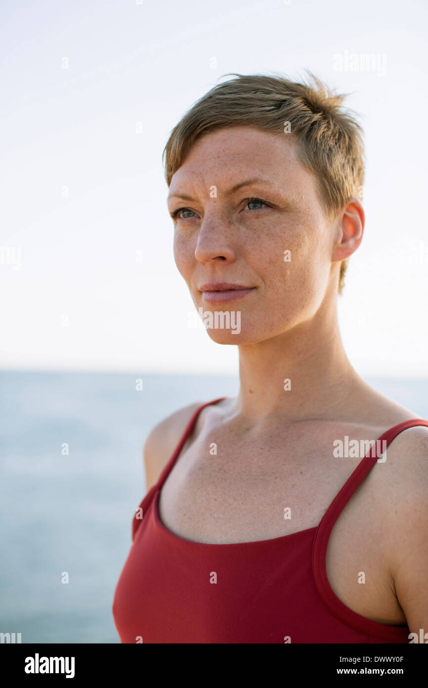 Thoughtful woman in spaghetti straps looking away against sea - Stock Image