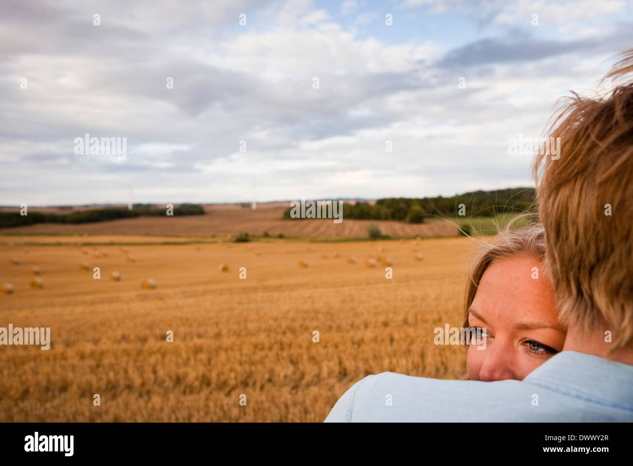 Cropped image of affectionate young couple at field - Stock Image