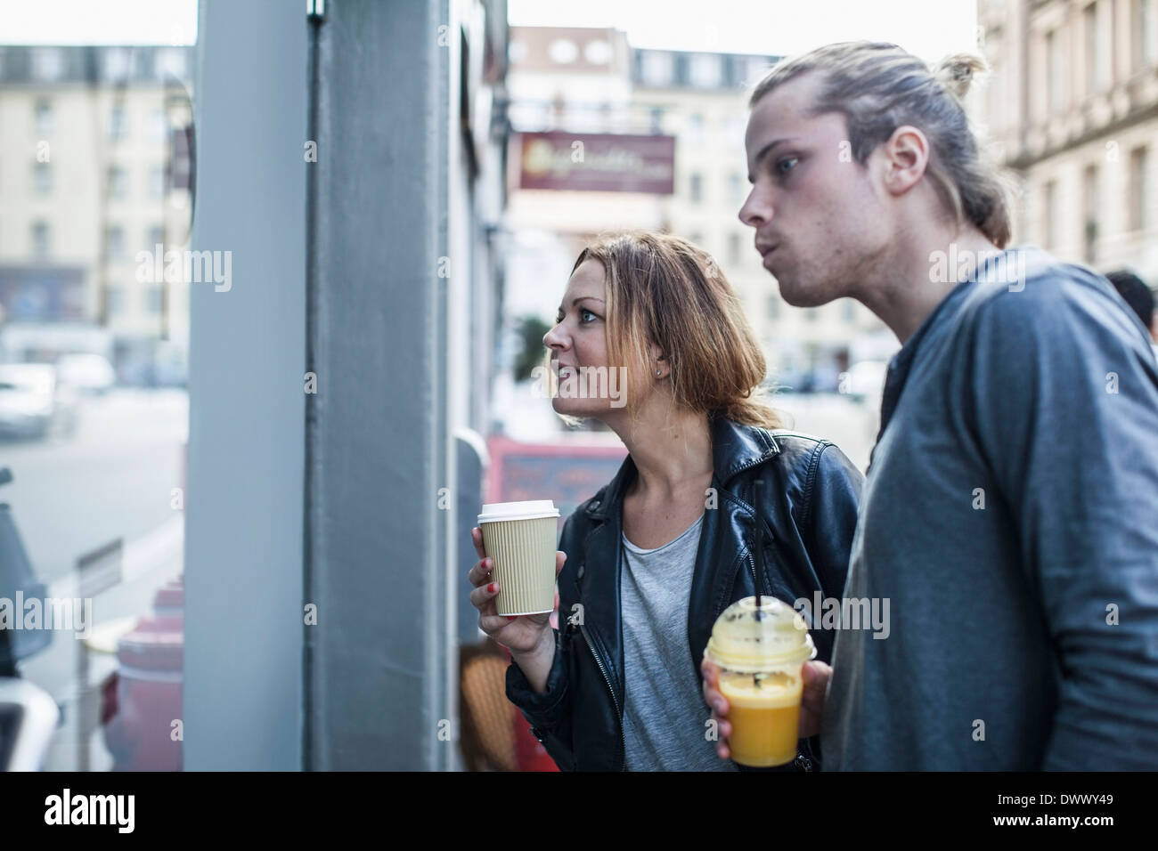 Couple holding disposable cups while window shopping - Stock Image