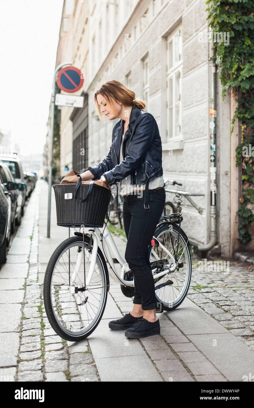 Mid adult woman searching for something into bag in bicycle basket at street - Stock Image