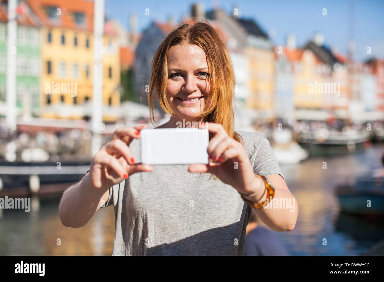 Portrait of happy woman photographing at harbor - Stock Image