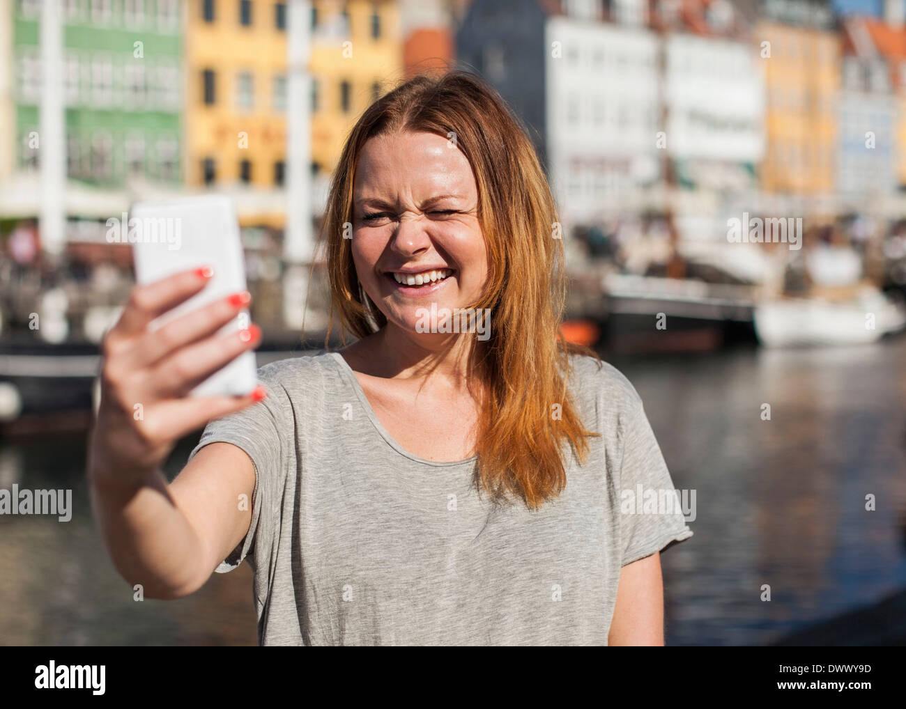 Happy woman photographing  through smart phone at harbor - Stock Image