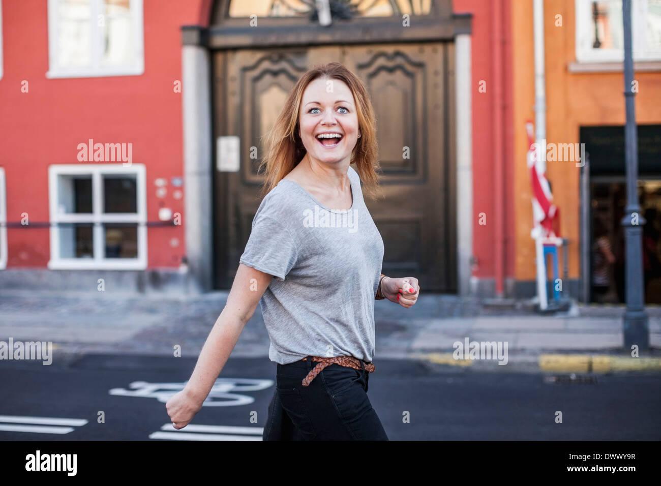 Portrait of happy mid adult woman walking on city street Stock Photo
