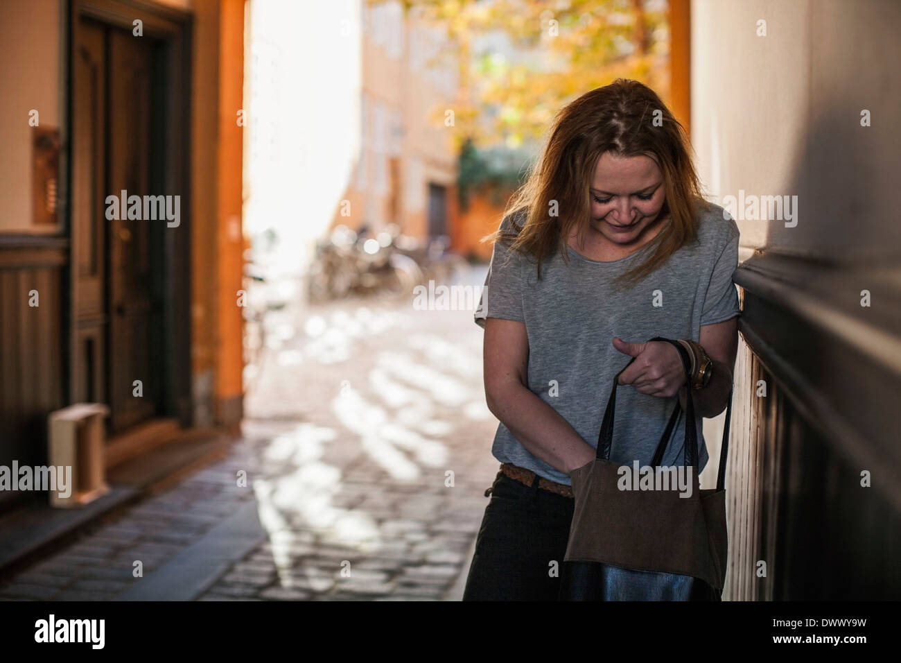 Mid adult woman searching something into purse - Stock Image