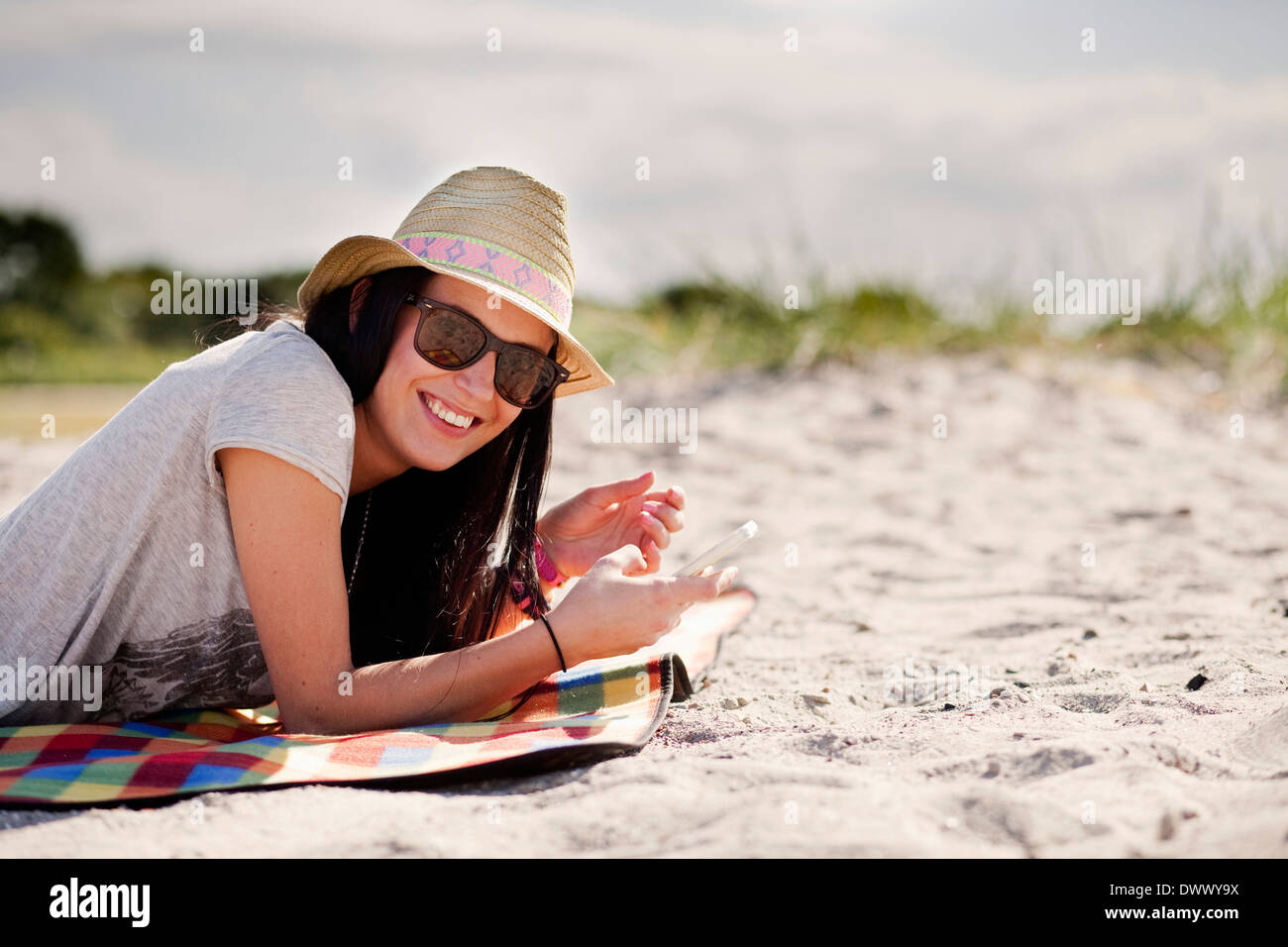 Portrait of happy woman holding mobile phone while lying on picnic blanket - Stock Image