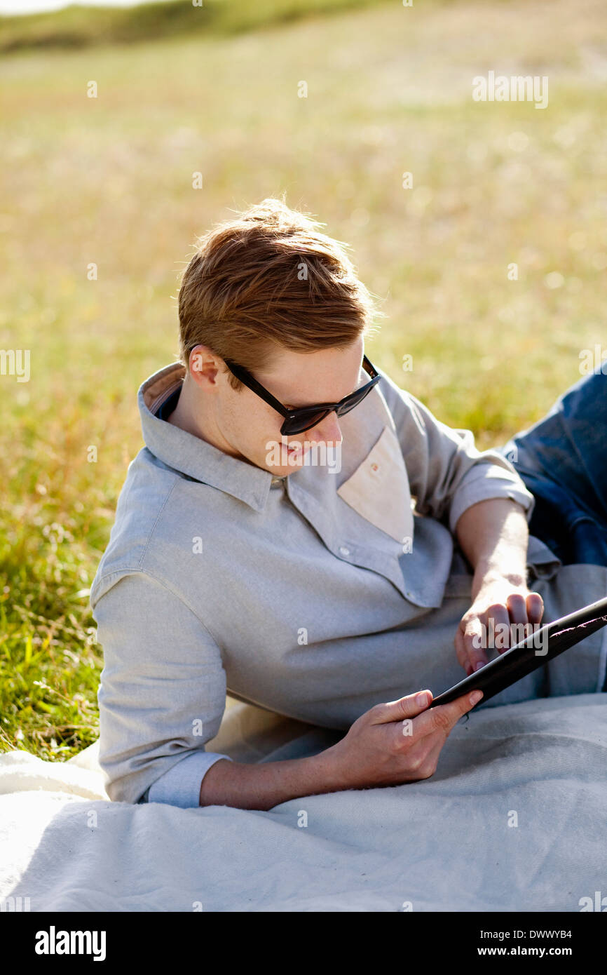 Young man using digital tablet while reclining on picnic blanket - Stock Image