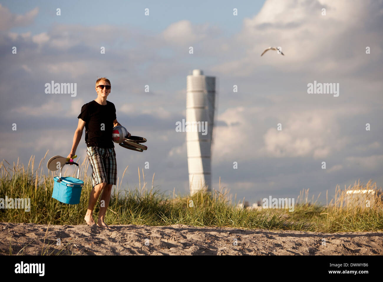 Young man carrying picnic equipment at beach - Stock Image